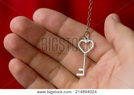 The key to the heart for true love. A man holds a key in the form of a heart on his palm. The man takes love