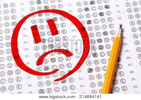 Incorrect negatively passed test sad face. Blank multiple choice answer sheet filled with pencil