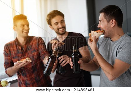 Men drink beer and eat pizza in the kitchen. They talk and have a great time. The three men met and chatted in a bright room.