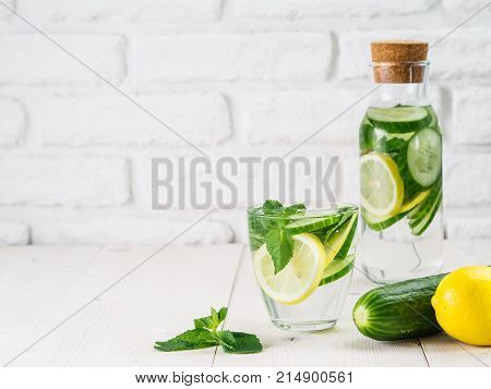 Infused detox water with cucumber, lemon and mint in glass and bottle on white table. Diet, healthy eating, weight loss concept. Copy space