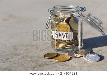 Coins in glass jar and on gray floor with sand background, copy space. Money box, saving money for dream, pension, vacation. Financial stability concept
