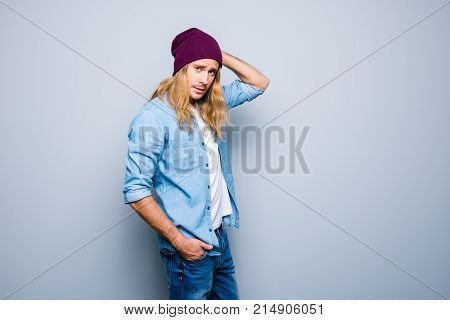 Handsome Young Guy With Stubble, Long Blonde Hair, Is Dressed In Denim Jeans Casual Outfit And Purpl