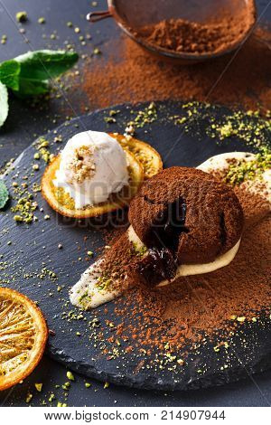 Exquisite french dessert. Chocolate fondant, creme anglaise and vanilla ice cream, sprinkled with cocoa powder, served on round slate finely decorated with orange citron and pistachio crumble, closeup