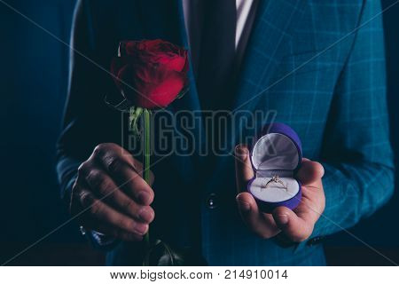 Close up shot of man in formal wear holding in one hand box with engagement ring and rose in another one. Will you marry me?