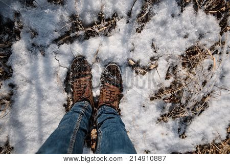Male legs in blue jeans and winter shoes on snow, close-up