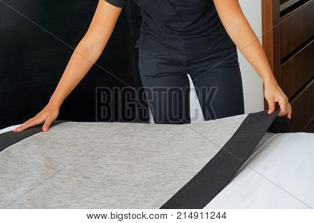 Maid making bed in hotel room. Maid Making Bed poster