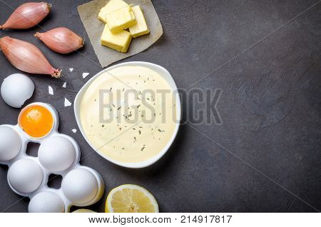 Homemade basic french sauce bearnaise in a white bowl with ingredients butter shallot lemon eggs on a black slate stone background with copy space top view