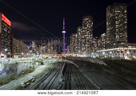 Skyline view of Toronto downtown at night. Many railroad tracks leading to the Union Station in the foreground. Province of Ontario Canada