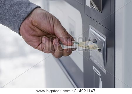 person's hand sticks a paper money bill into the banknote bill acceptor