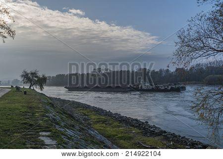 Big cargo boat in Devin village on Dunaj river in autumn morning