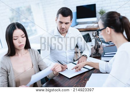 The couple went to a lawyer to conclude an agreement on the divorce. They quarrel and argue with each other. Lawyer prepares documents.