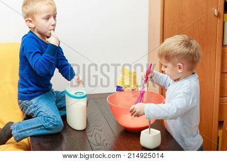 Healthy diet for children youngsters cooking concept. Two kid boys cooking making cake in bowl