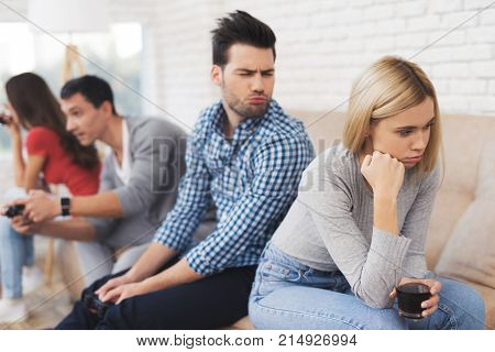 Two guys and two girls play on the game console. They are sitting on the couch and holding the joysticks. Girls are offended by the guys.