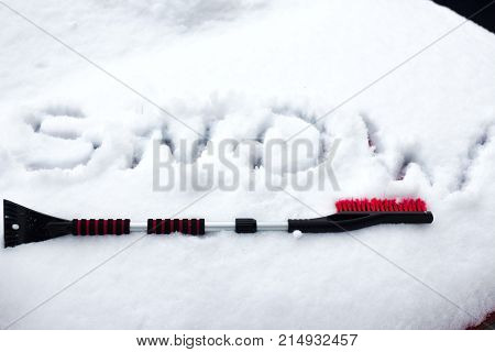 Hand In Black Glove Removes Snow From Car Windshield In Winter Day