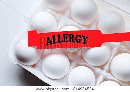 Allergy bracelet over top a carton of eggs