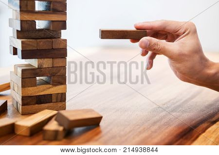 Business Man Placing Wooden Block On A Tower Concept Of Risk Control Planning Risk And Strategy.