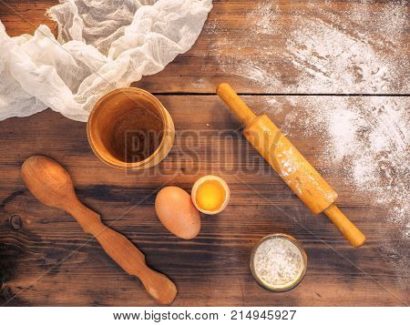 Still life on the background of the old wooden table, top view in rustic style with kitchen utensils. Spilled flour, salt, egg yolk, fabric, wooden spoon and rolling pin.