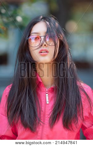 Asian woman fashion portrait. Sensual seductive lovely and beautiful mixed race asian caucasian young girl in pink jaket and red sunglasses looking at camera outdoor against green blurred bokeh city background. Gorgeous slim model posing outside on the st