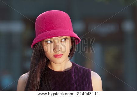 Attractive asian woman fashion portrait. Beautiful romantic mixed race asian caucasian young girl in pink hat jaket looking away outdoor against blurred bokeh city background. Gorgeous slim model in trendy glamour stylish clothes waiting someone outside i