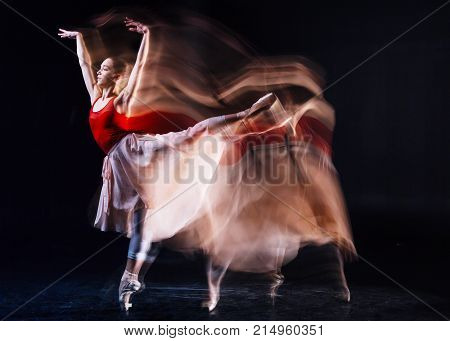 Professional ballet dancer. Skillful beautiful female dances raising her leg and looking in front of her while dancing ballet