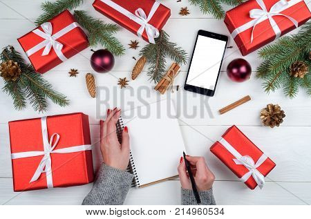 Female writing goals to blank notebook christmas gifts copy space. Mom writes to do list of gifts for Christmas and New Year. Top view flat lay. Mobile phone with white screen for app presentation