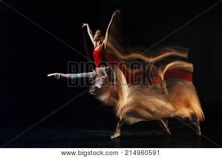 Dancing movement. Nice skillful attractive woman holding her hands up and jumping while performing the dance