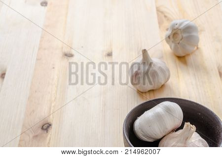 Garlic In Black Bowl On Wooden Table Background