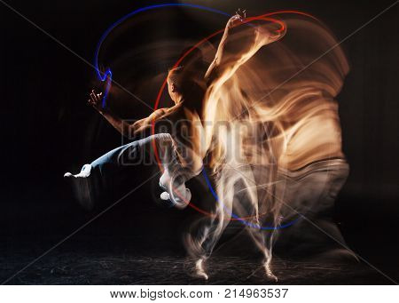 Outstanding skills. Attractive pleasant skillful man standing against black background and jumping up while showing his skills