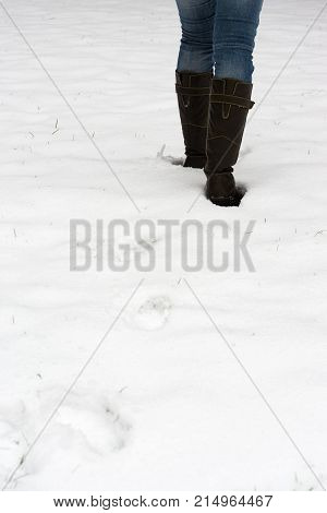 rear view of female legs in boots walking through fresh snow leaving behind footprints