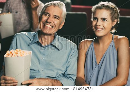 Happy senior Caucasian man sitting in cinema holding popcorn between young Asian and Caucasian women, watching movie and smiling