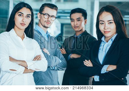 Closeup portrait of four proud young business people looking at camera and standing with arms crossed and cafe interior in background