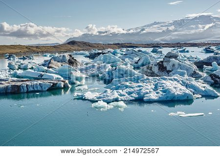 Beautiful vibrant picture of icelandic glacier and glacier lagoon with water and ice in cold blue tones, Iceland, Glacier Bay, icebergs in the water