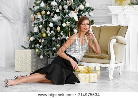 Christmas, winter holidays concept. Beautiful charming woman in evening dress with a gift box. Luxurious apartments decorated for Christmas. Beauty, fashion.