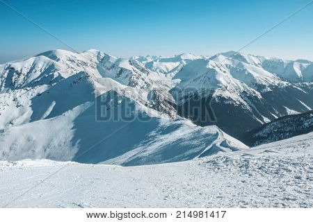 Nice mountains view at sunny day with blue sky with sun light at winter time.