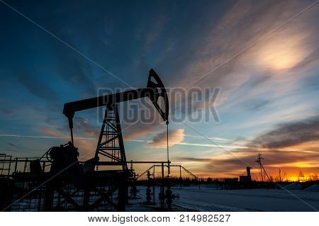 Pump jack at sunset sky background. Extraction of oil. Petroleum concept.