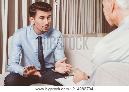 Excited young businessman sitting on sofa, gesturing, talking and looking at senior partner who is sitting opposite to him back to camera