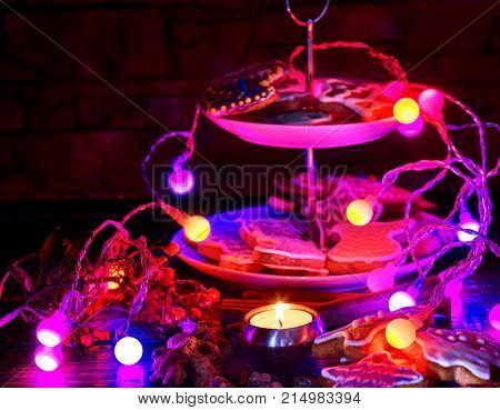 Candle light table with Christmas gingerbread cookies and Xmas garland and star sweets decoration tiered cake stand on table and burning candles.