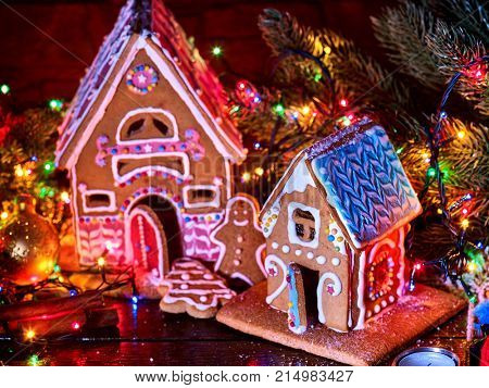 Ginger bread houses with Christmas garland. Xmas food gingerbread man cookies decorating holiday village table with burning candles.