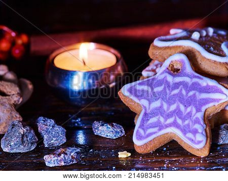 Christmas gingerbread cookies and cinnamon stick and star sweets are on wooden table and burning candles. Xmas still life object.