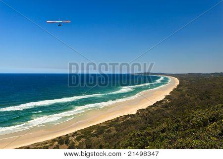 Hang Glider Flying Over Beach In Byron Bay Au