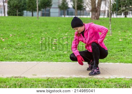 Young woman exhausted after train on a cold winter day on the training track of an urban park. Female athlete wearing pink windbreaker, beanie, gloves and running tights