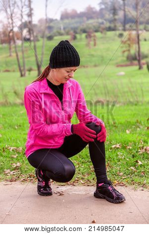 Female athlete hurting from a knee injury on a cold winter day on the training track of an urban park. Young woman wearing pink windbreaker, beanie, gloves and running tights
