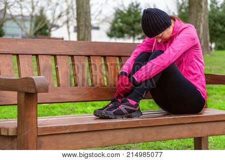 Female athlete tired or depressed resting on a bench on a cold winter day on the training track of an urban park. Young woman wearing pink windbreaker, beanie, gloves and running tights