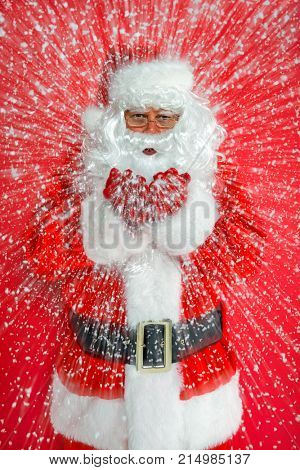 Santa Claus or Father Christmas blowing snow towards you against a red background.