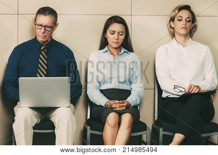 Five serious businessmen and businesswomen sitting in row at wall and waiting for job interview. Senior man is working on laptop. Young man is sleeping on shoulder of middle-aged woman who is writing.