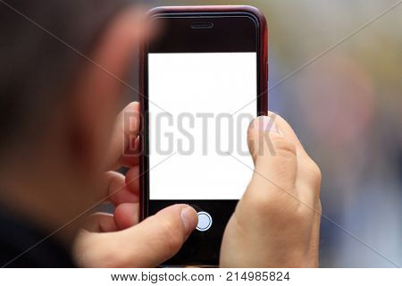Smartphone blank screen template with copy space in man's hands. Blurred background