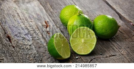Cut and whole limes on wooden table, copy space
