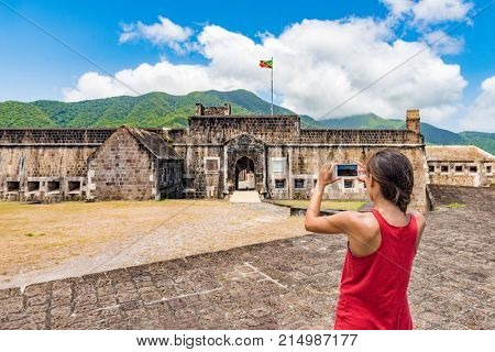 St Kitts tourist woman taking picture on cruise ship travel vacation. Girl visiting St. Kitts Brimstone Hill Fortress National Park on St Kitts and Nevis. Caribbean destination cannon lookout.