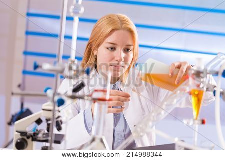 Female laboratory assistant with chemical experiment in scientific laboratory