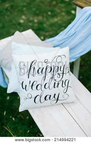 event, wedding, decoration concept. on the garden bench there is snowy white pillow with engagement congratulation printed in italic type of vintage style with different curlies